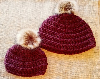 crochet mommy and me beanies in burgundy maroon with tan and brown faux fur pompom.
