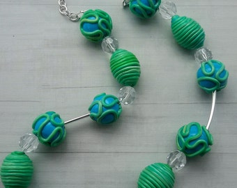 gorgeous beaded statement necklace with swirly green,blue beads on silvery chain