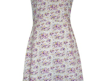Sleeveless dress in white cotton printed with flower patterns