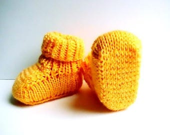 Orange baby booties in acrylic