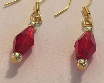 Red earrings dangle. Red dangle earrings. Red earrings. Red drop earrings. Gold trim, hangs on gold ear wires.