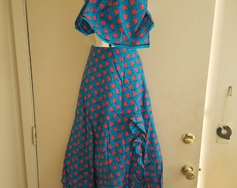 A medium blue with red spotted long skirt with a neck scarf or head wrap