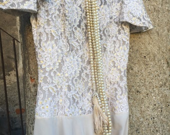 Sartorial dress in ivory lace and silk with pearl necklace and Nappette dating back to the 1920s