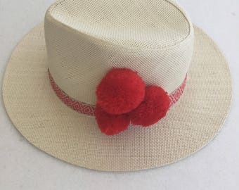 Red pom pom straw hat