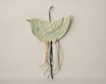 Oiseau en céramique à accrocher avec  rubans et dentelles, émail dans les tons pastel, vert pâle,bleu, impressions de feulles