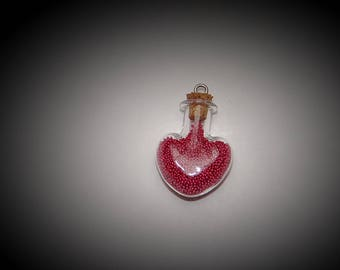 A glass vial filled sandblasted raspberry heart shape