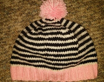 Knitted black, white and pink hat with pom pom