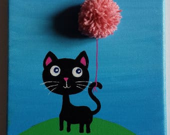 A black cat with a pink ball hanging from his tail