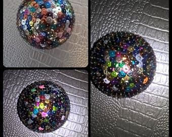 Styrofoam ball embellished with sequins to ask