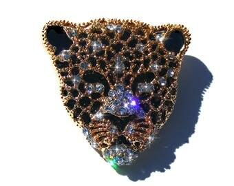 Broche tête de léopard doré, émaux noir et strass blanc.