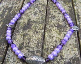 Purple beaded necklace with moon and triple spiral charms
