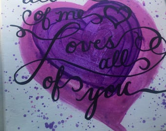 "Pink and purple painted heart sign with ""all of me loves all of you"" quote."
