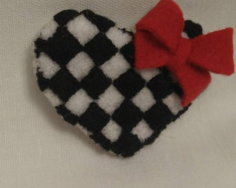 Black and white pin with red bow