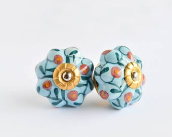 Blue hand painted ceramic knobs with a flower design with gold metal