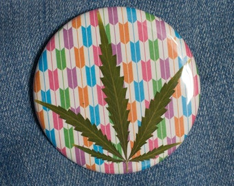 Pressed Cannabis Leaf Button on Pink, Orange, Turquoise, Purple & Green Background.
