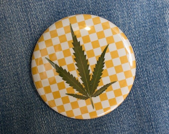 Pressed Cannabis Leaf Button on Orange Checkered Background