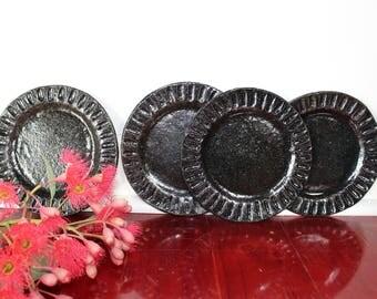 Set of four black glazed ceramic sandwich plates