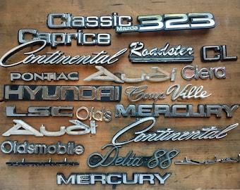 vintage car emblem badges, large lot carnages lettering logos, man cave decor, garage signage, plastic and metal
