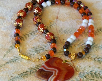 Beautiful colors of orange and brown. 20 in beaded necklace with 2 inch dyed agate pendant.