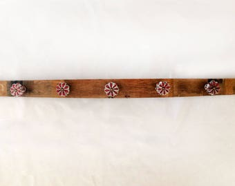 wall coat rack with red vintage style knobs on a repurposed rustic wine barrel stave