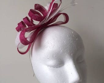 Pink and white loop facinator with white netting and feathers on a headband.