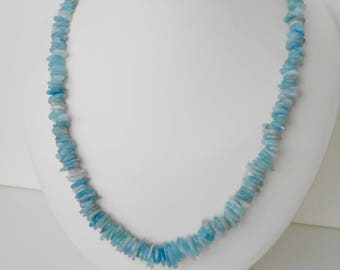 Aquamarine necklace of graduated slices of Aquamarine with sterling silver clasp measuring 24 inches.