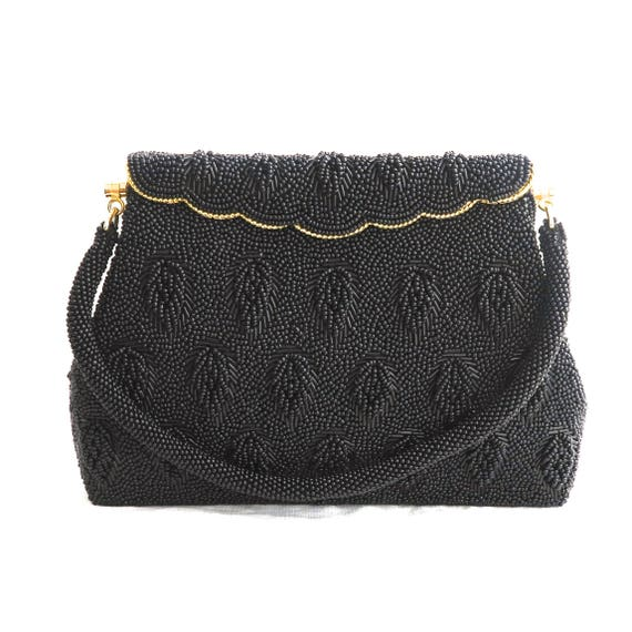 Mid 20th century black beaded purse with foldover front with gold metal trim, bugle and seed beads in pattern of falling leaves, circa 1960s