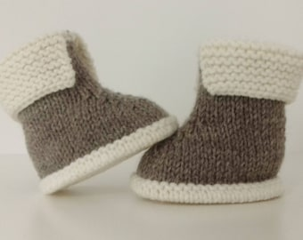 Let us put on bootees baby birth in 12 months knitting(sweater) woolen hand is in hiding and ecru