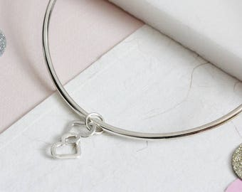 silver bangle with two entwined linked hearts charm