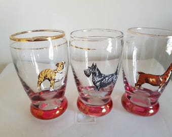 Three small liquer glasses featuring dogs