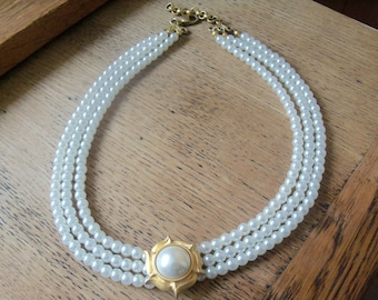 Elegant triple strand faux pearl collar necklace with large pearl cabochon in sunburst motif