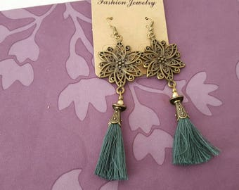 bronze earrings with connectors in the shape of flowers and dark bronze glass bead with green PomPoms