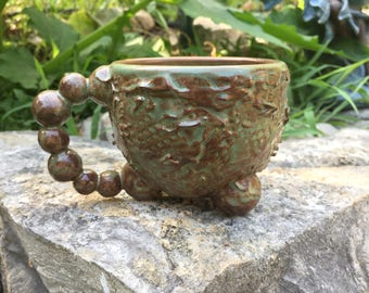matte green and brown tripod mug with textured structure motif