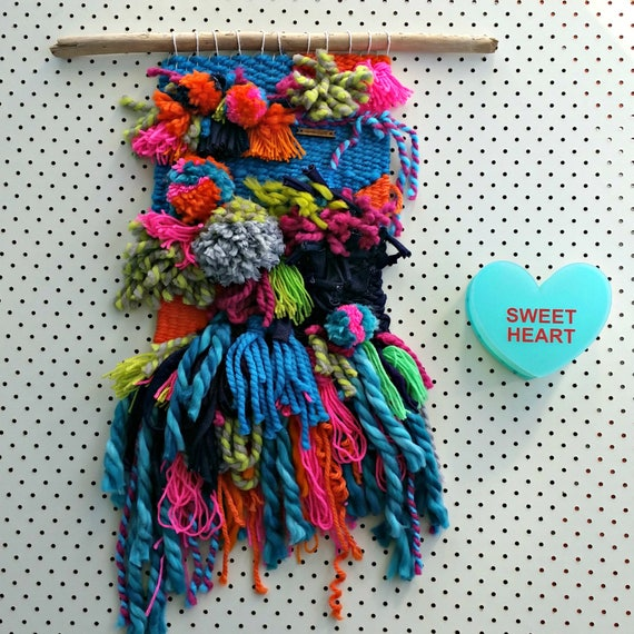 Woven wall hanging. Fibre art. Made from yarn scraps. Bright, colorful textural with pom pom detail. Modern weaving. Interior decor