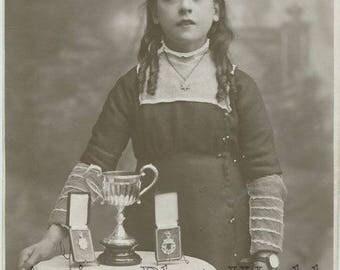 Girl singer posing with medals singing awards strange antique photo
