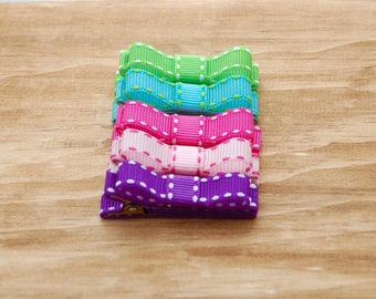 Double prong alligator clips fully lined in bright green , aqua , hot pink , light pink and purple grosgrain with stitch and tuxedo bow