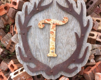 Metal antlers on weathered wooden sign with stone inital rustic wall decor