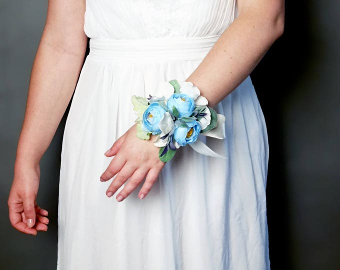 Wrist corsage with paste blue peonies, white hydrangea and greenery