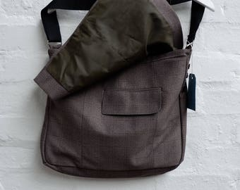 Over-the-shoulder messenger bag. Made from a recycled mans suit jacket. Light brown checked pattern with olive green lining.