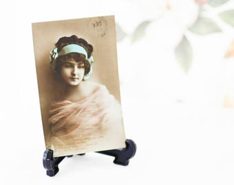 Real Tinted Photo Postcard by Paul Fink Berlin; a beautiful Flapper-style girl wearing a green hairpiece, circulated in England, c1910s