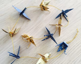 Garland of blue and gold paper origami cranes
