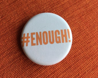 "Set of two. Enough! 1.25"" pinback button. In ""safety orange."" Give one to someone you love."