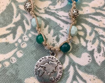 """Boho hemp necklace with """"Not all who wander are lost"""" pendant and blue and silver glass beads"""