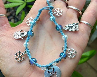 Frozen themed light blue hemp bracelet with clear, blue and pearl glass beads. Snowflake, reindeer, castle and snowman charms