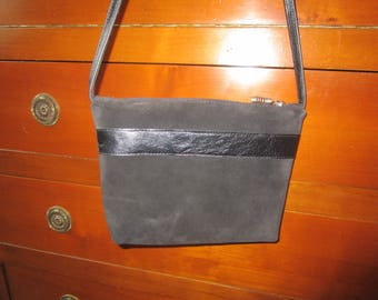 Black nubuck leather clutch bag has shoulder strap