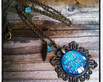 cabochon pendant necklace has blue and gold sequin with charms