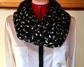 Black infinity scarf has white feathers