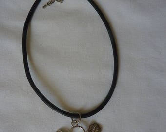 Pendant has leaves on a large waxed cord