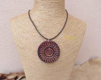 Crew neck dark brown leather oriental motif pendant