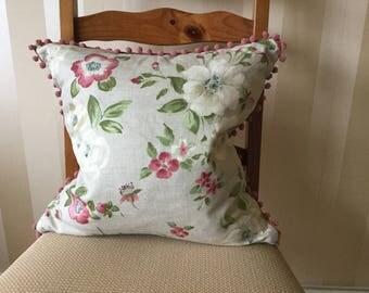 Cushion with pom pom trim detail